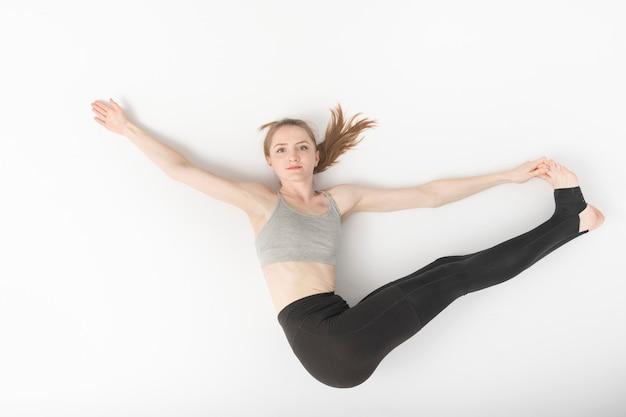 若い女性は体操に従事しています。柔軟性の開発。ヨガのアーサナ。美しいほっそりした女の子は白い背景の上のハタヨガを行います