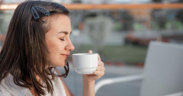 若い女性は、屋外の夏のテラスで彼女の朝のコーヒーを楽しんでいます