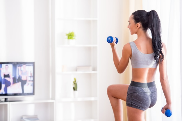 Young woman is exercising with dumbbells at home.