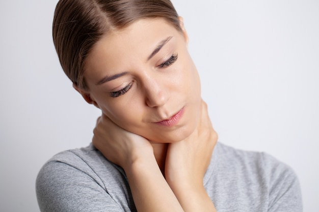 Young woman is experiencing severe neck pain