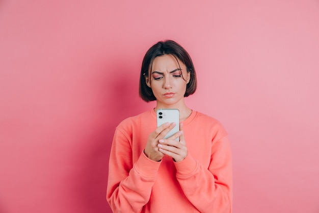 若い女性はピンクの背景の上に、彼女の携帯電話を使用してsmsを読んでいる間悲しい不幸な怒りを感じています
