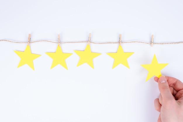 Молодая женщина дает свой отзыв, помещая пятую звезду в рейтинг, держа маленькую звезду на изолированном белом фоне