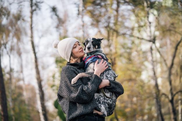 若い女性は彼女の腕の中で犬を保持しています。