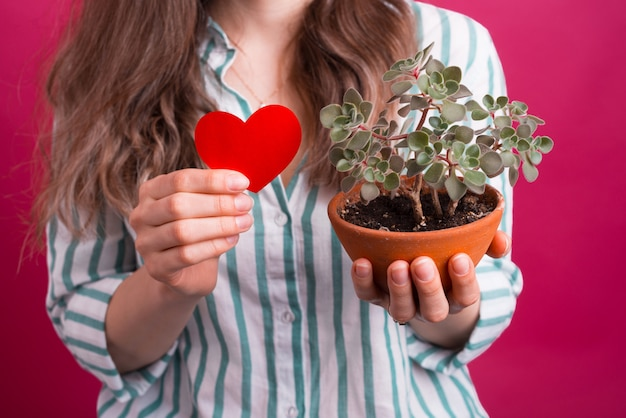 若い女性は愛と鉢植えの赤いハートを持っています。