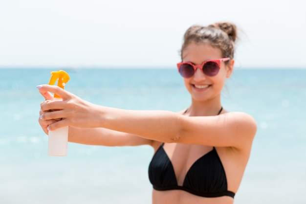 Young woman is holding a bottle of sunblock for body at the sea background.