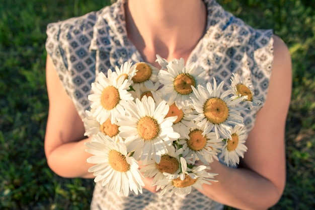 A young woman is holding a bouquet of chamomile in her hands.