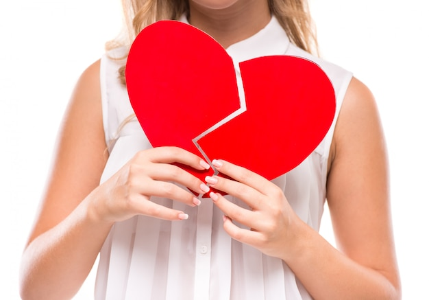 Young woman is holding a broken heart isolated.