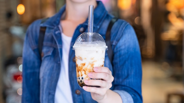Young woman is holding drinking brown sugar flavored tapioca pearl bubble milk tea with glass straw in night market of taiwan close up bokeh