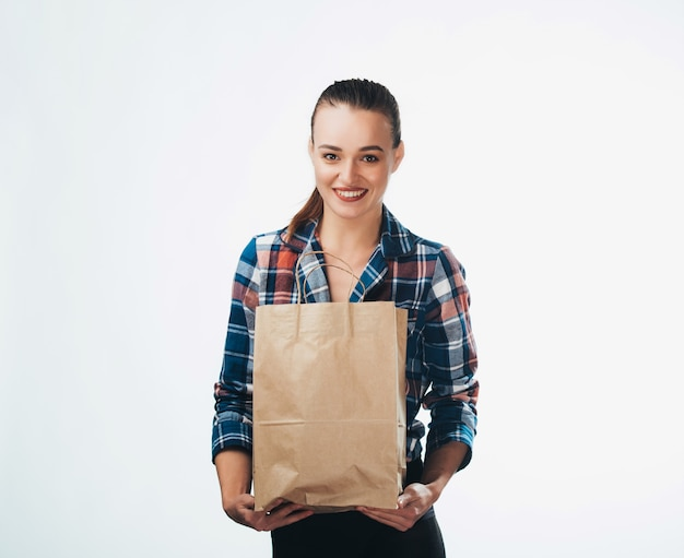 Young woman is holding grocery shopping bag on white background. young girl is looking in camera. isolated background. closeup.