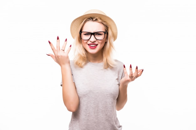 Young woman is holding her face in astonishment, isolated over white wall