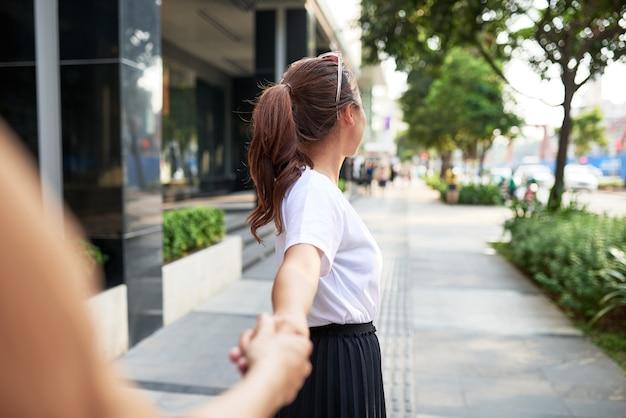 若い女性がホーチミン市のルロイ通りで夫婦の手を握っています。