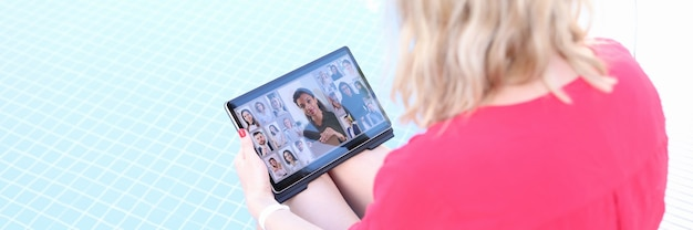 若い女性は、プールの端に座っている間、タブレットを介してオンラインビジネス会議を開催しています