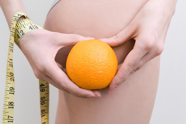 Young woman is holding an orange and a measuring tape on a light background. cellulite problem concept