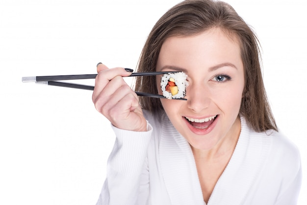 Young woman is holding piece of sushi rolls on her eye