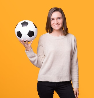 Young woman is holding a soccer football ball over yellow background.