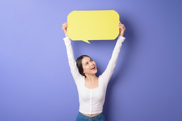 Young woman is holding yellow empty speech on purple background