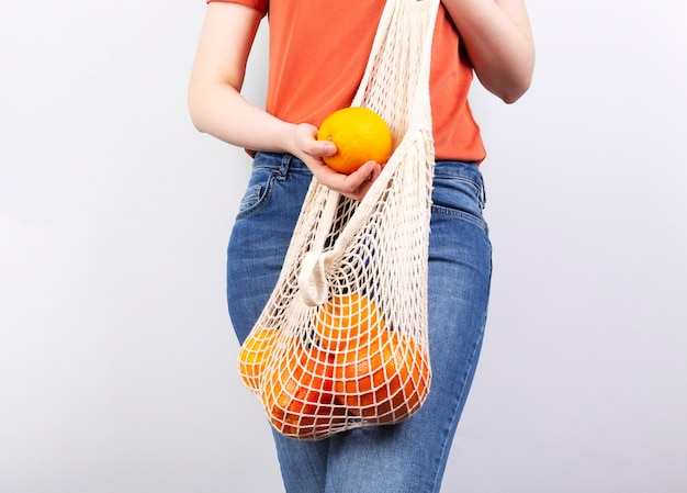 Young woman is on holds string bag with various citrus on grey background