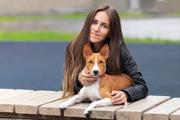 Молодая женщина обнимает свою собаку басенджи терьера