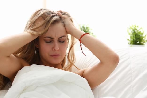 젊은 여자는 머리가 아파서 침대에 누워있다