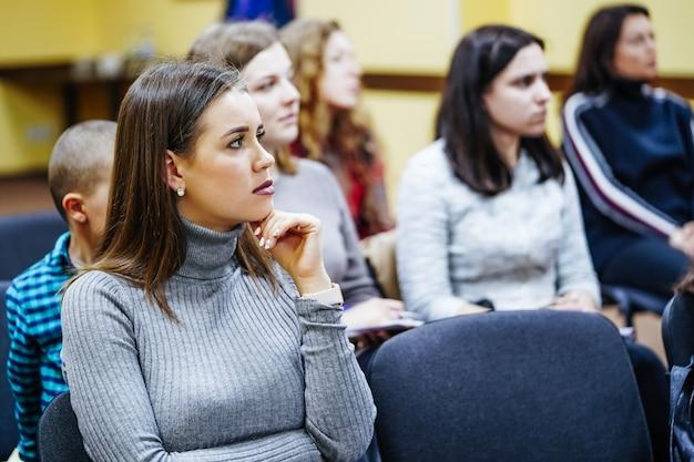 Молодая женщина слушает на конференции или семинаре. красивая женщина в аудитории. крупный план. выборочный офис.