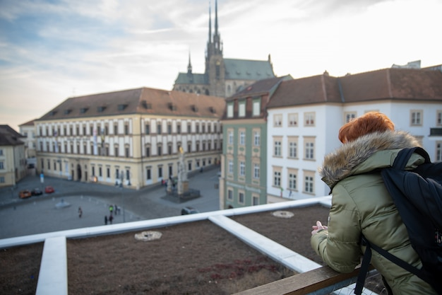 Young woman is looking at brno from a viewing terrace. take pictures of the city on the phone and share it on the social site
