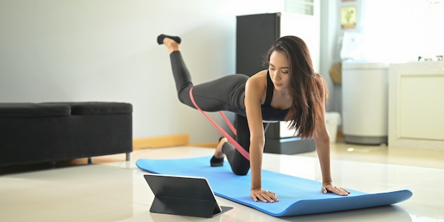 A young woman is looking into a computer tablet while doing an exercise on the exercise mat