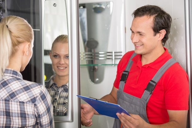 Young woman is looking in the mirror, plumber is smiling.