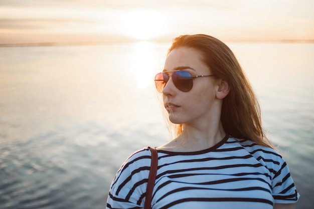 Young woman is looking at the sunset over a sea or river with beautiful soft sunny reflections in water
