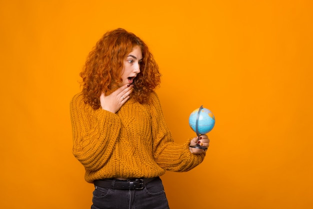 Young woman is looking surprised at globe on orange wall.