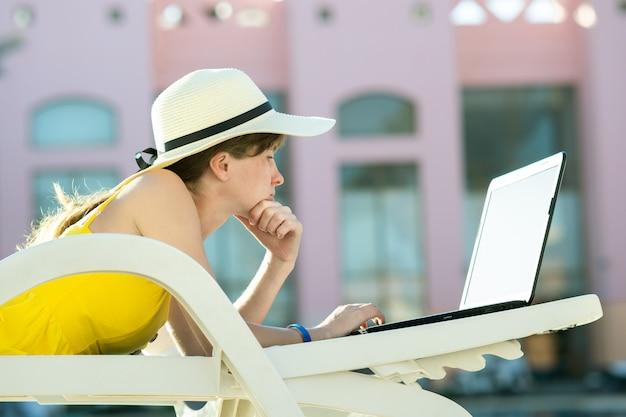 若い女性は、夏のリゾート地でキーにテキストを入力する無線インターネットに接続されているコンピューターのラップトップに取り組んでいるビーチチェアに横たわっています。
