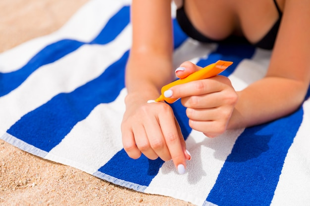 Young woman is lying on striped towel on the sand at the beach and applying sun cream on her hand.