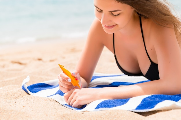 Young woman is lying on the towel at the beach and applying sunbclock from the tube on her hand.