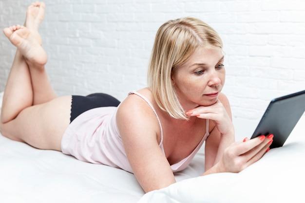 Молодая женщина лежит с планшетом в постели. блоги, онлайн-общение, дистанционное обучение и социальные сети.