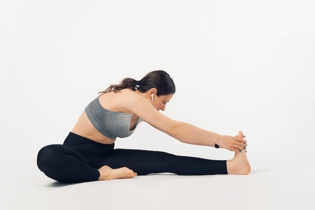 若い女性は、イヤポッドで音楽を聴きながらストレッチ体操をしています。