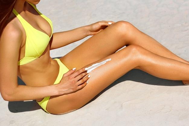 젊은 여성이 해변에서 일광욕을하는 동안 선 스크린 로션을 마사지하고 있습니다.