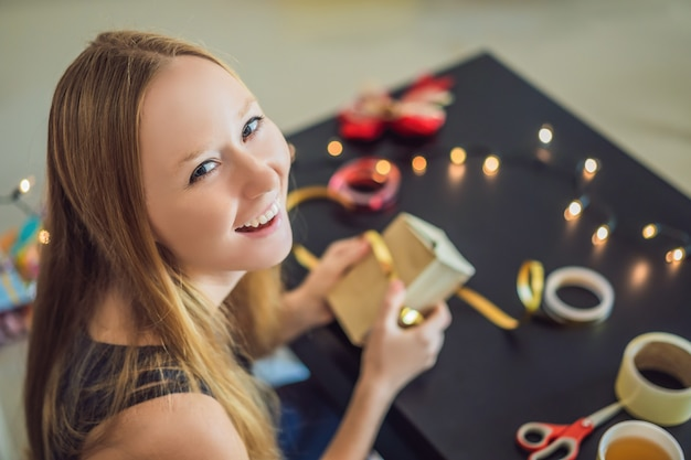 젊은 여자는 선물 포장입니다. 크리스마스를 위해 빨간색과 금색 리본으로 공예 종이에 싸인 선물