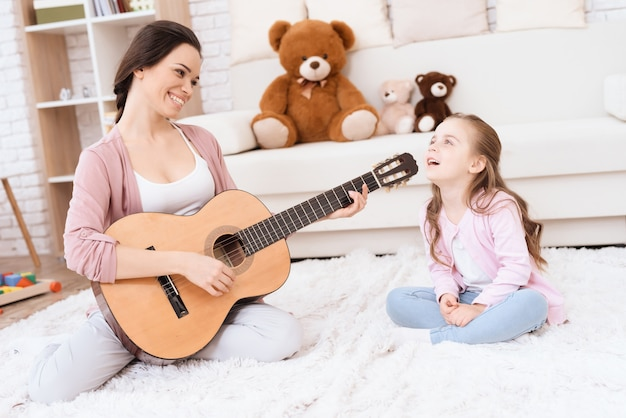 A young woman is playing guitar, and a girl is singing.