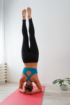 若い女性は、逆立ちをしながら、自宅でヨガを練習しています。白い背景に