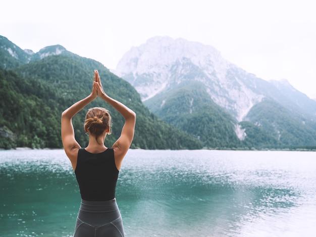 Молодая женщина занимается йогой на горном озере. девушка занимается йогой на природе. здоровый образ жизни.