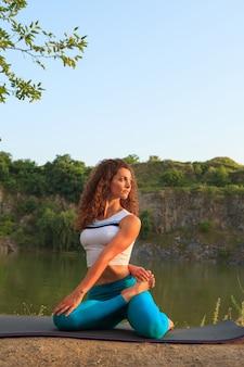젊은 여자 강 근처 요가 연습