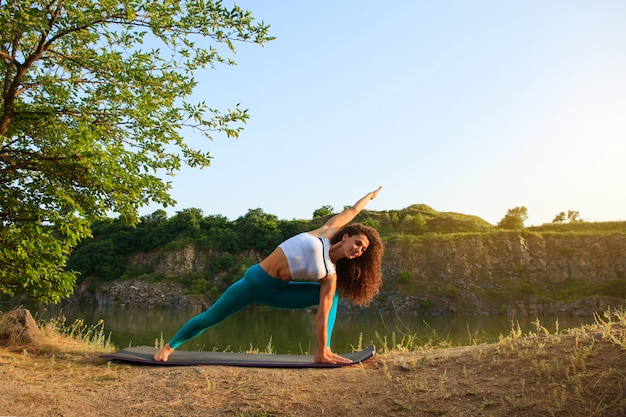 La giovane donna sta praticando yoga vicino al fiume