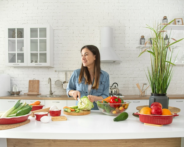 Young woman is preparing a salad in the kitchen .