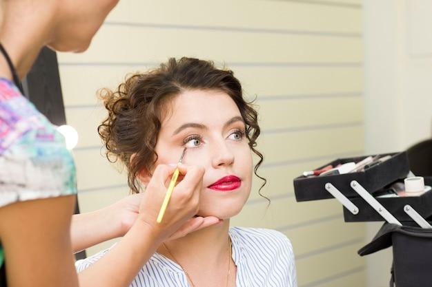 若い女性が美容院で化粧をしている