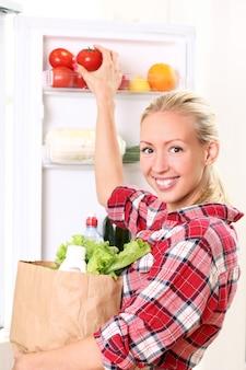 Молодая женщина кладет еду в холодильник
