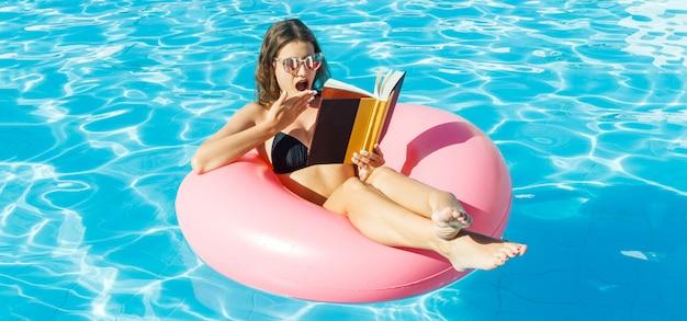 젊은 여자는 수영장에서 풍선 반지에 앉아 책을 읽고 있습니다.