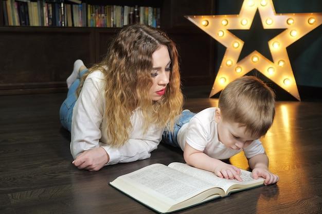 Молодая женщина читает книгу с маленьким сыном, лежащим на полу дома в гостиной после рабочего дня. традиция семейного чтения.