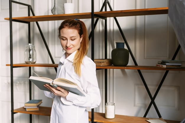 Young woman is reading a book in front of a stylish bookcase
