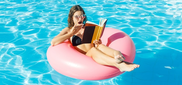 Young woman is reading a book sitting on the inflatable ring in the swimming pool.