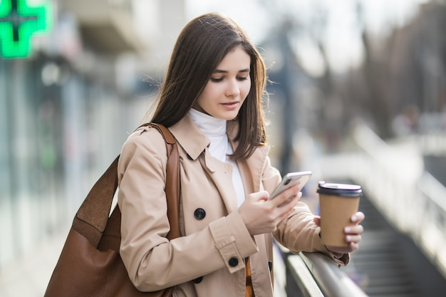 Young woman is reading news on her phone outside