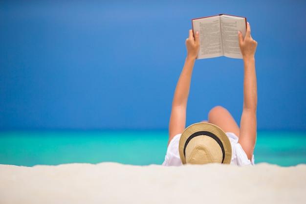 Молодая женщина читает на тропическом белом пляже